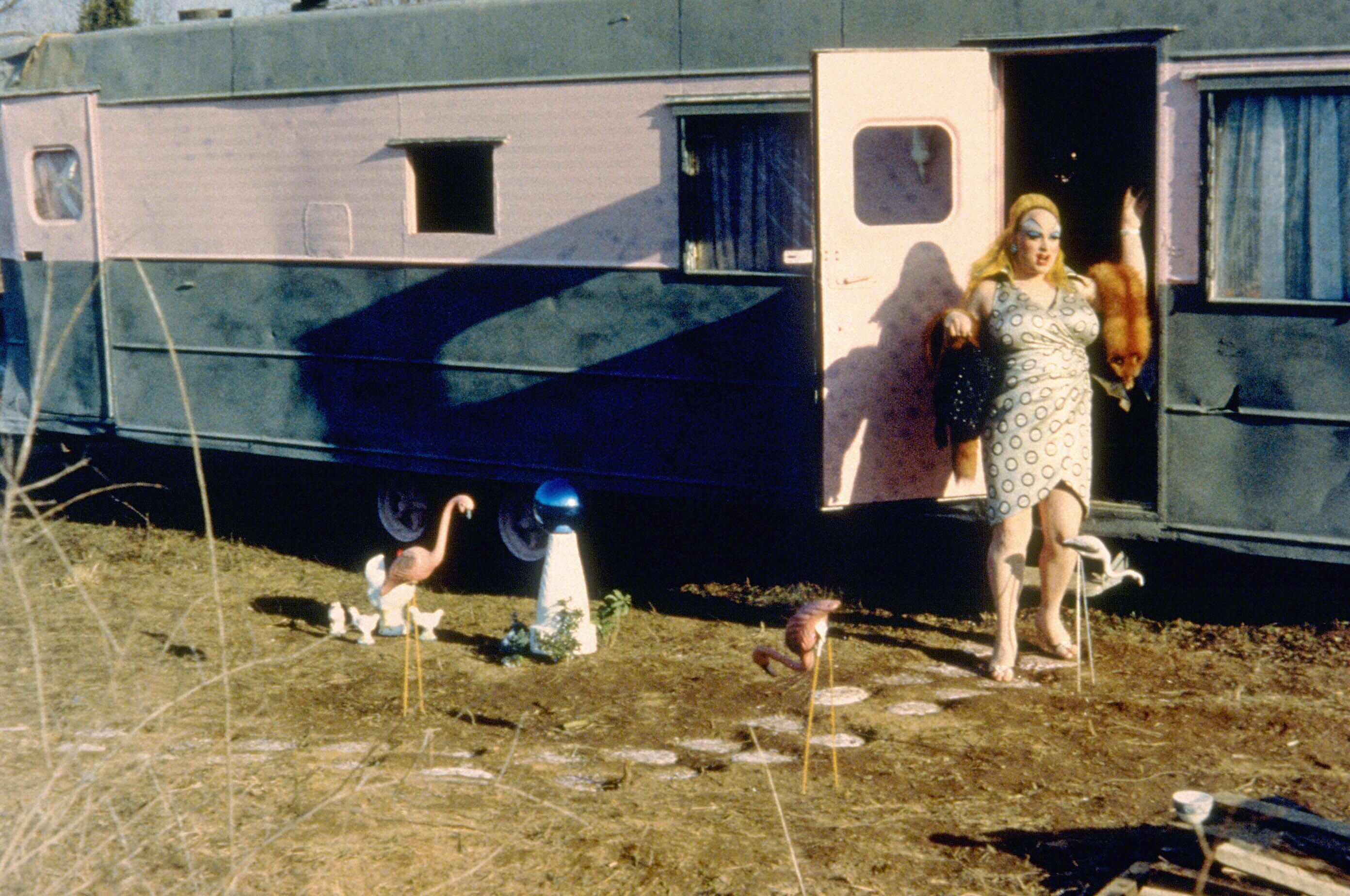 Divine stands outside her trailer in pink flamingos