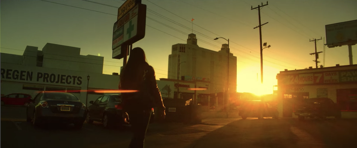 A character from Tangerine walks towards the sunset