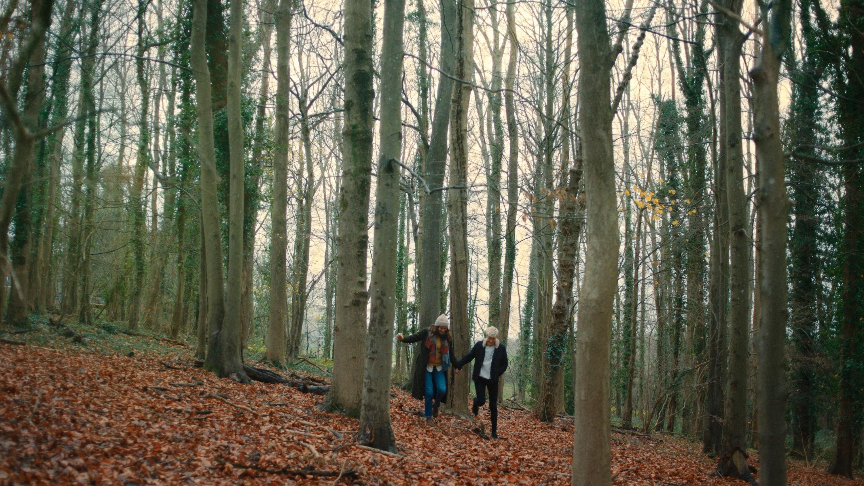 Mae walking through a forest