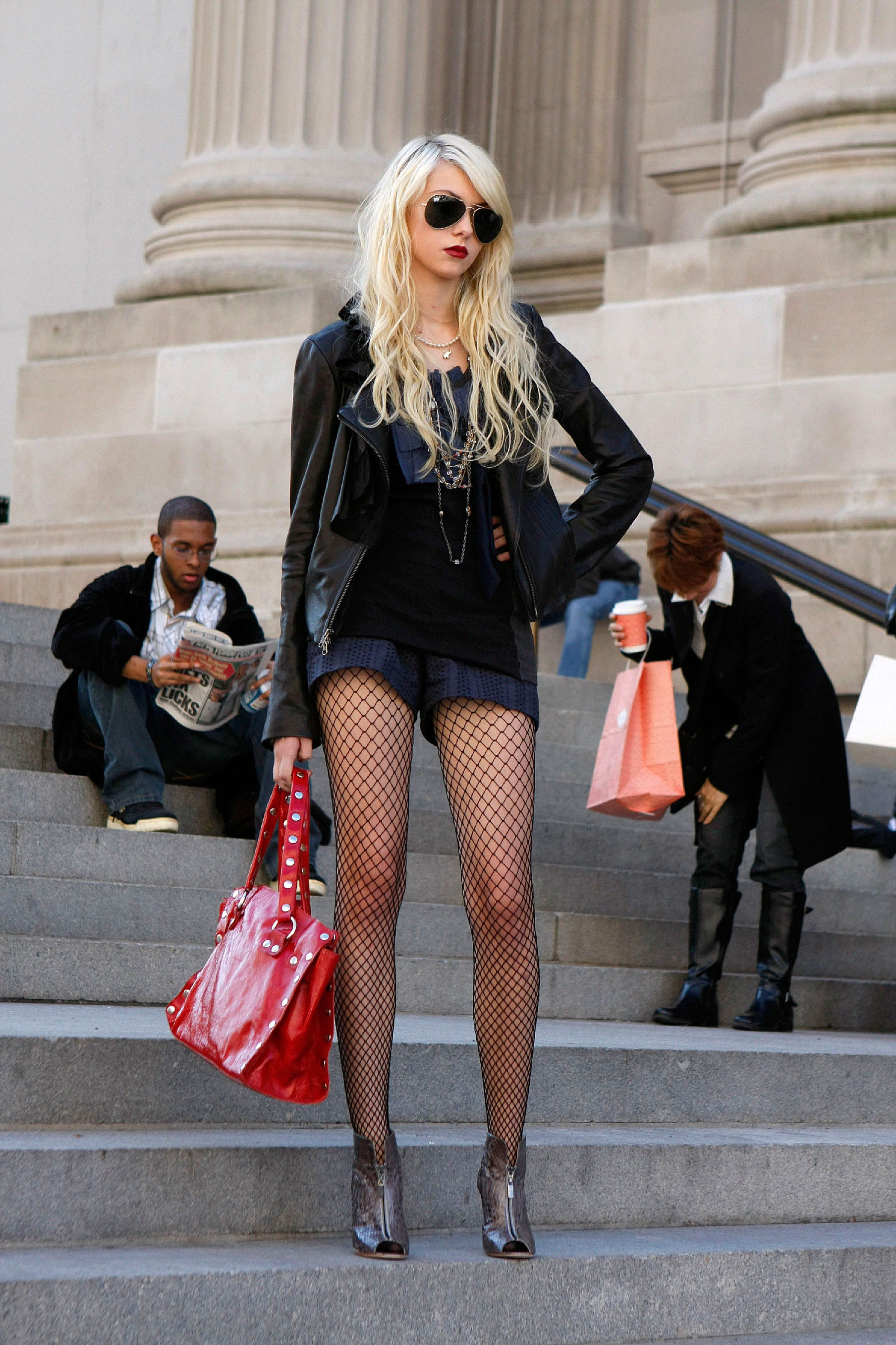 Jenny in a romper with a leather jacket and fishnets and a long necklace