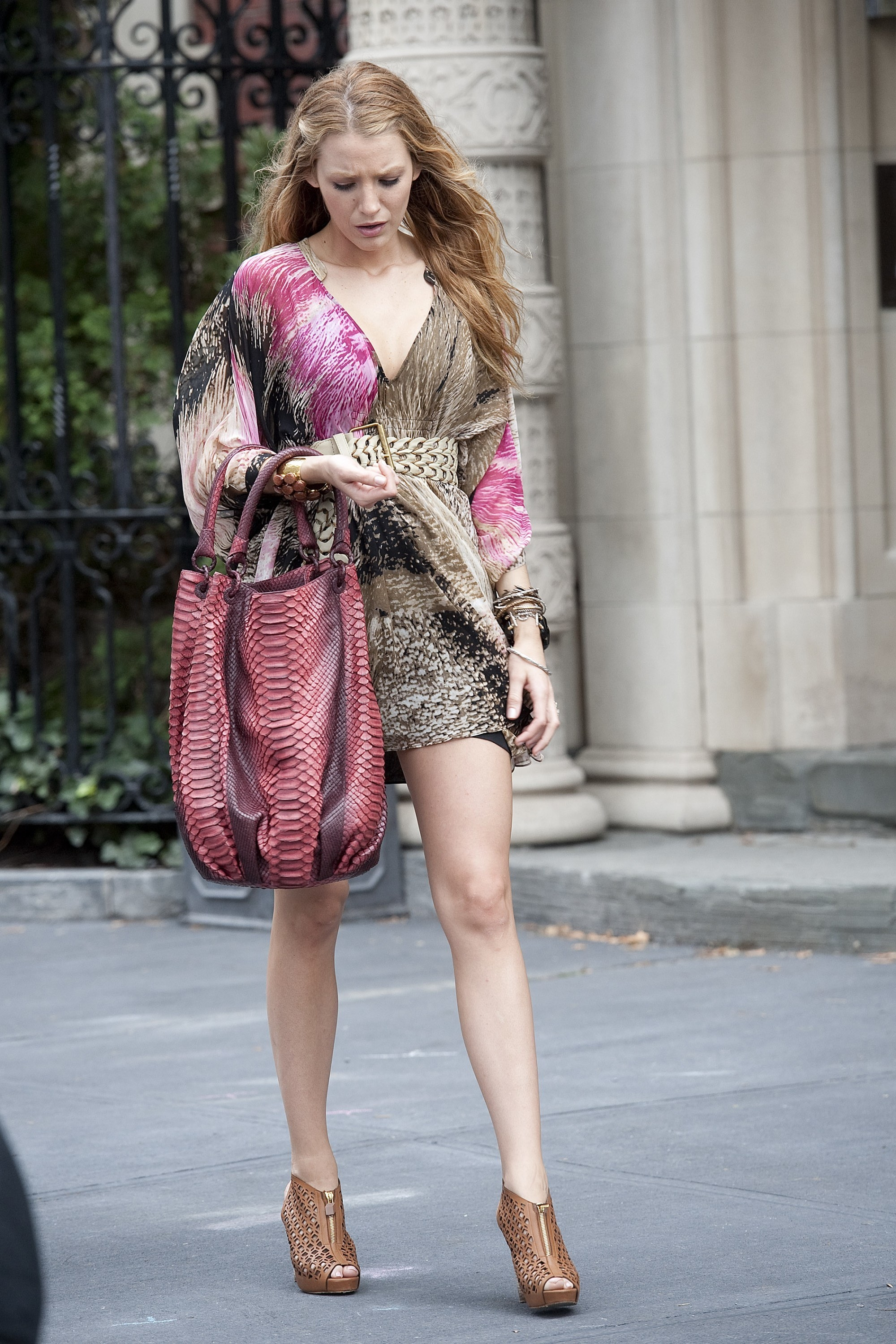 Serena in a loose v neck long sleeve tie dye short dress with a braided belt and booties