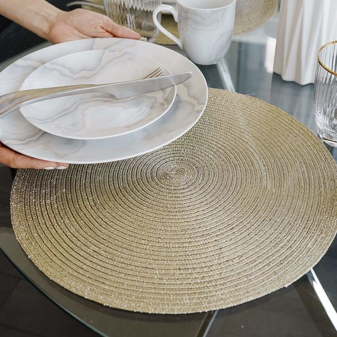 person putting plates on the placemat