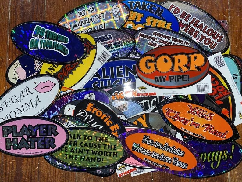 A large pile of Socially Hazardous stickers on a table