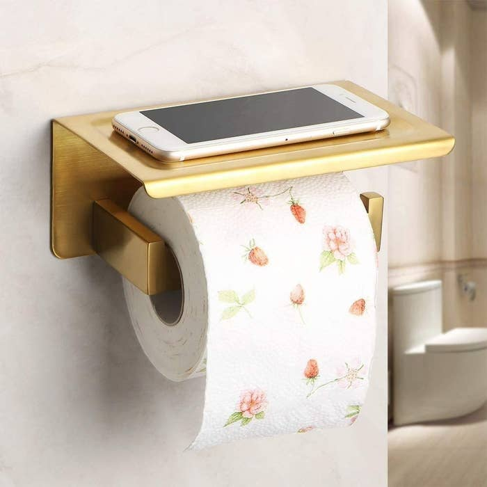 the holder with a phone and toilet roll on it