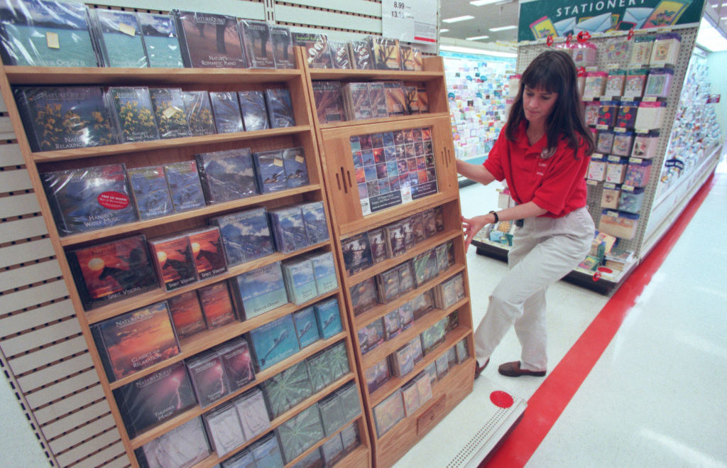 Photo of Target employee fixing large wooden Nature Sounds CD display