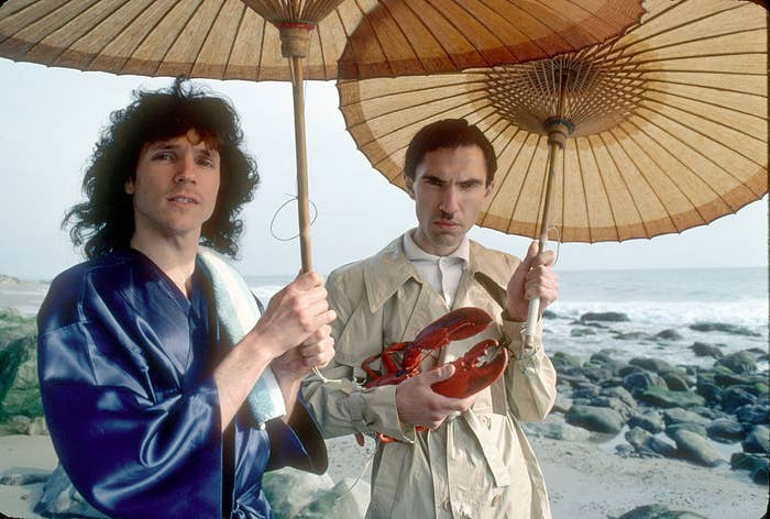 Russell wearing a silk robe and Ron wearing a trench coat, holding a fake lobster, both holding parasols, at the beach
