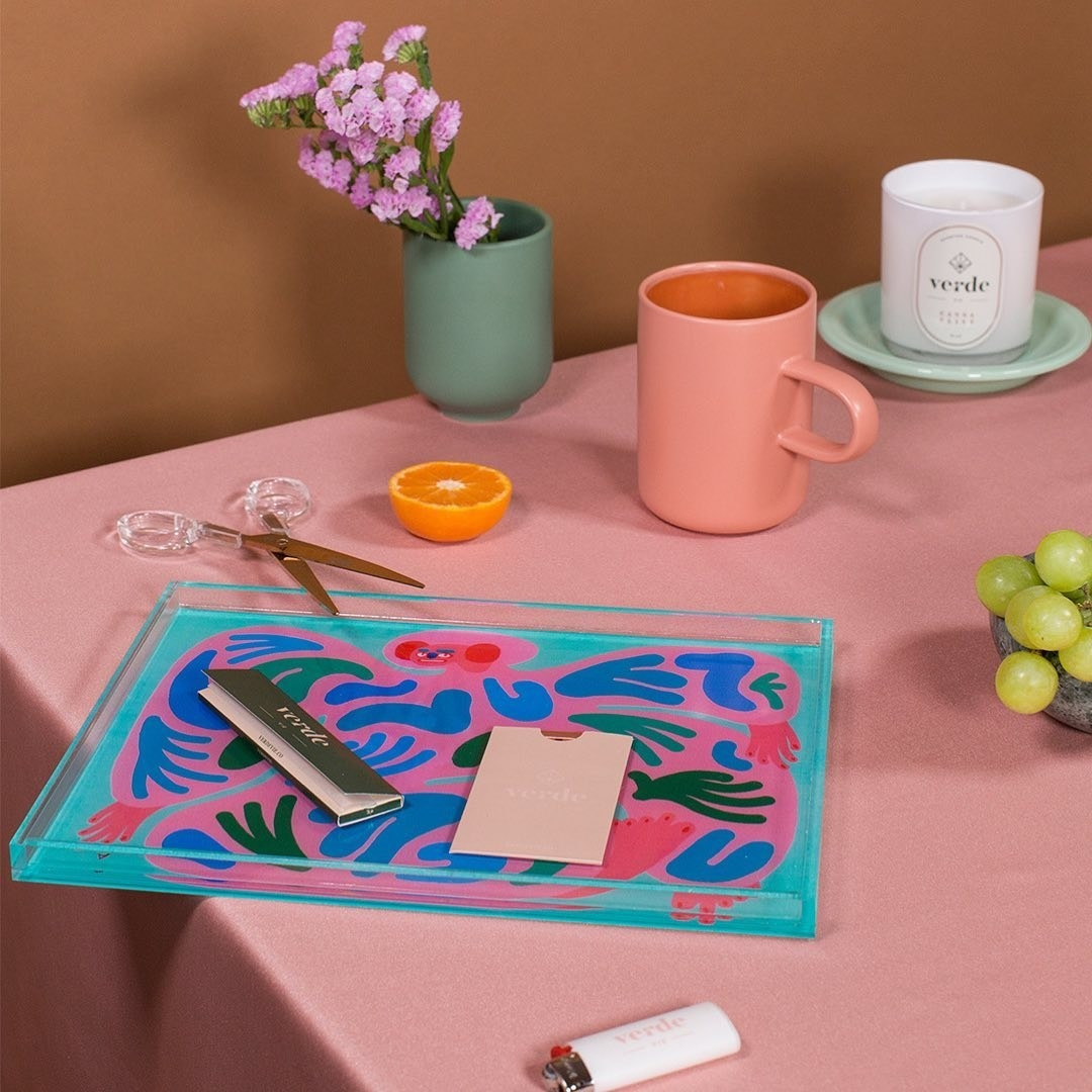 an instagram post of the vibrant lucite tray with a design of a creature on it filled with abstract shapes in blue green pink and red