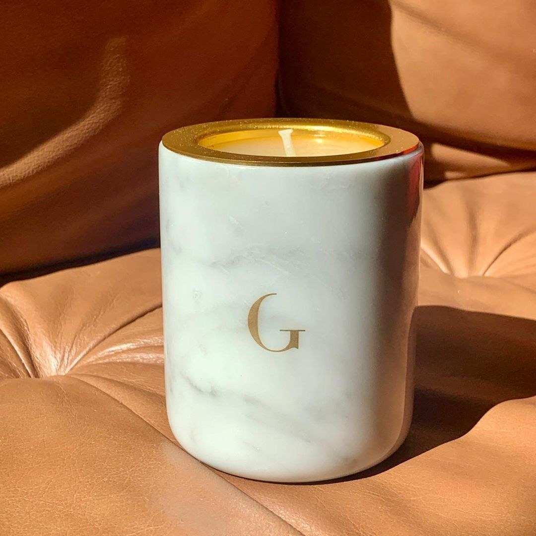 white marble candle sitting on a leather chair