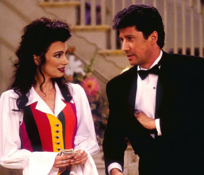 Fran wears a rainbow striped vest over a white blouse with puffy sleeves