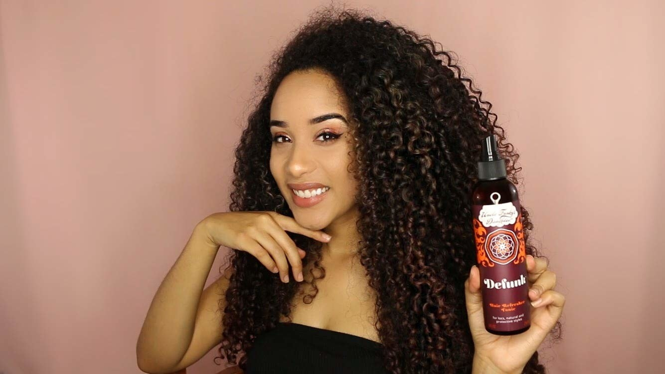 Model holding bottle of Defunk Hair Odor Neutralizing Tonic