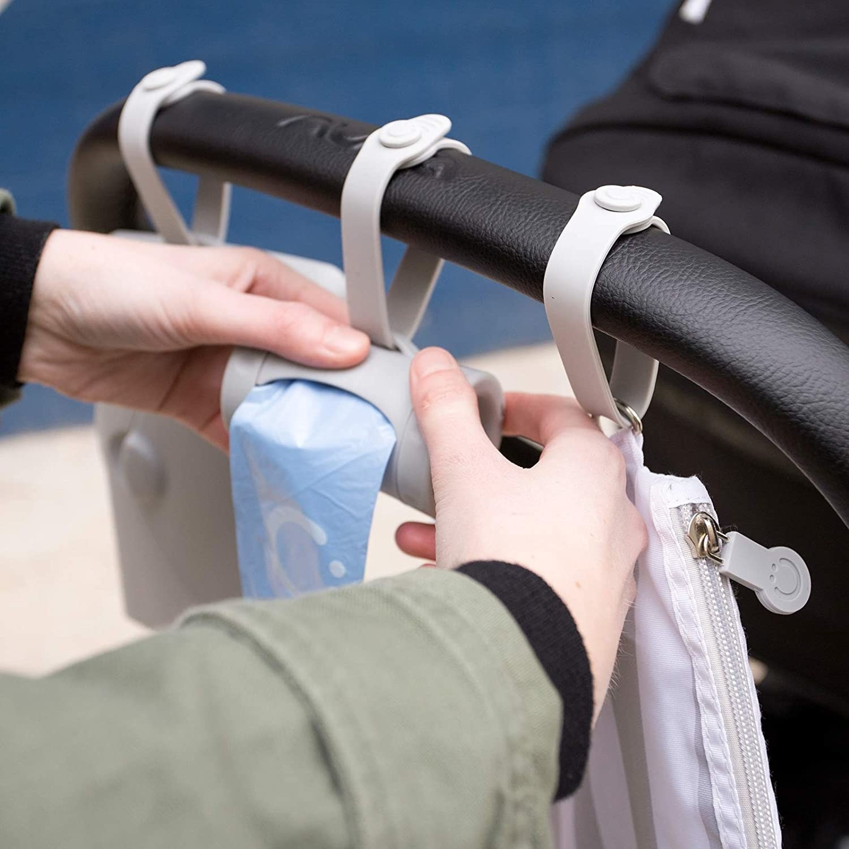 Diaper sack dispenser hung over stroller handle