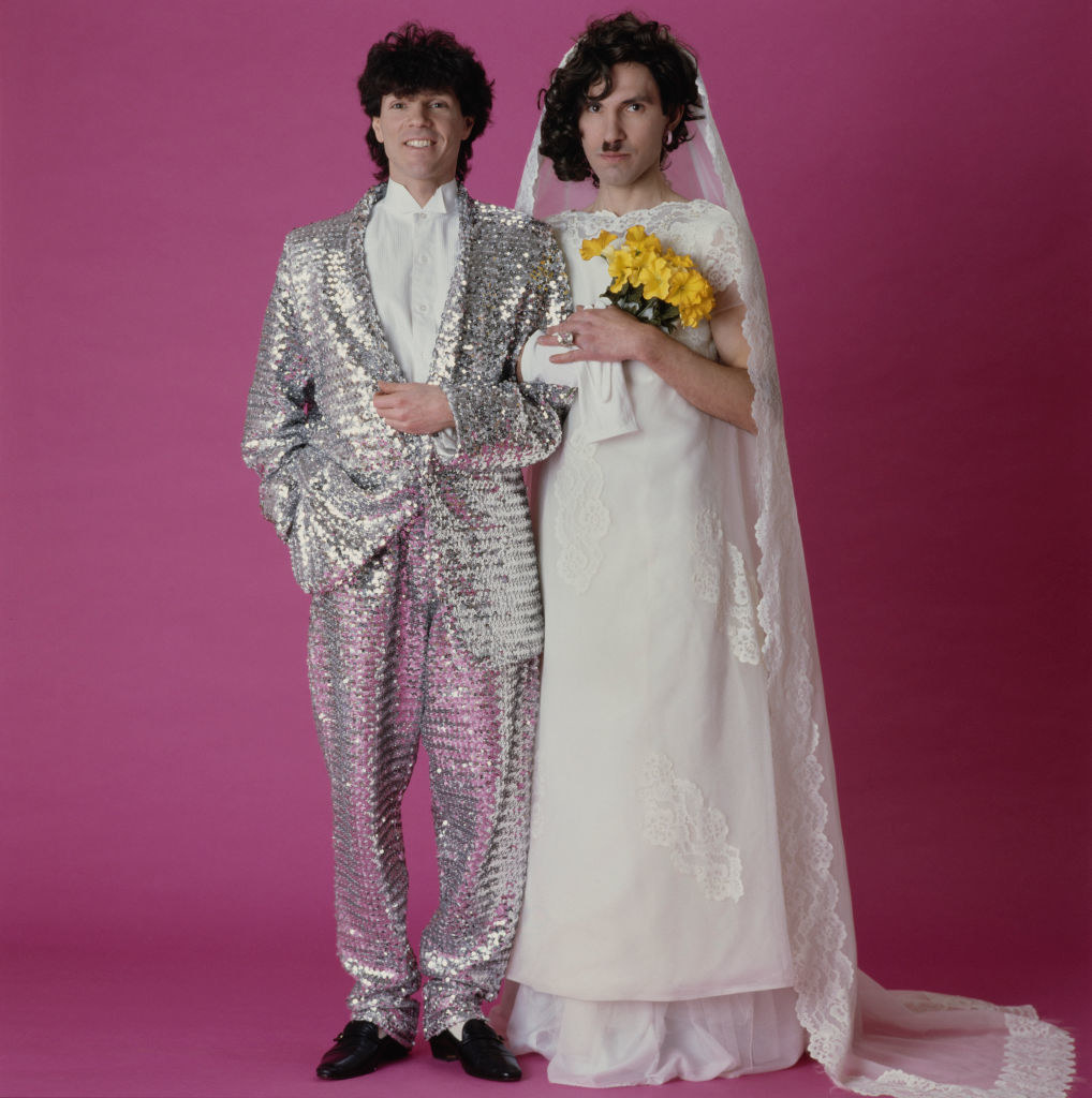 Russel and Ron dressed as a couple getting married in the 1980s, posing for an album cover
