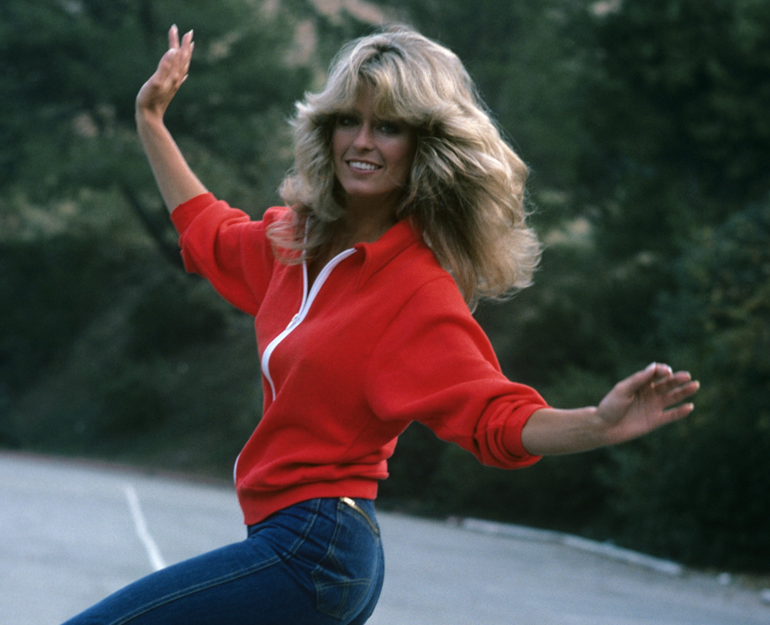 A young Farrah smiles while holding her hands out and wearing a red sweatshirt