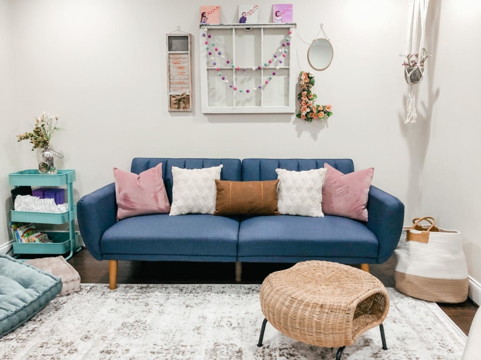 Reviewer's navy blue velvet futon adorned with pink, white, and rust-tone accent pillows in a room filled with wicker tables and baskets