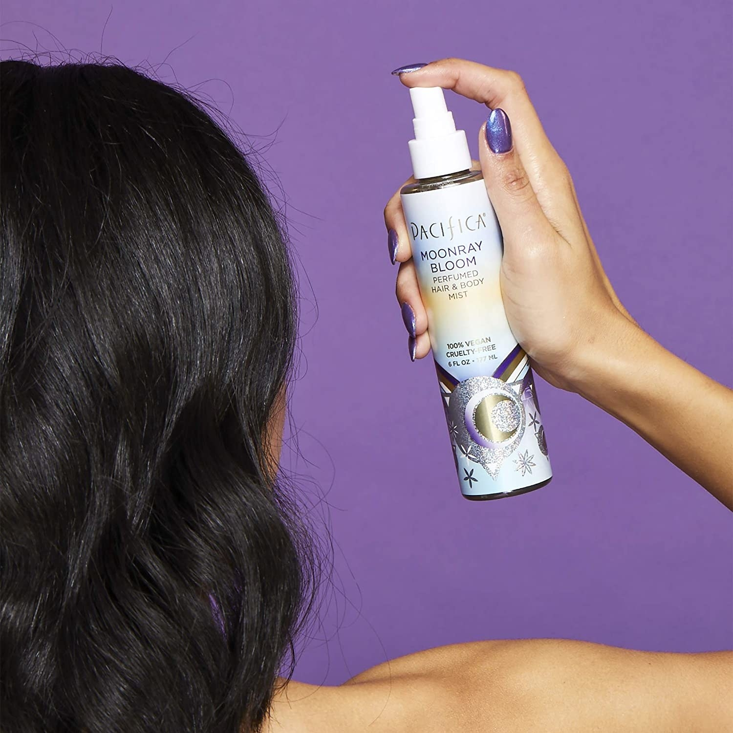 Model holding bottle of Pacifica Moonray Bloom Hair and Body Mist