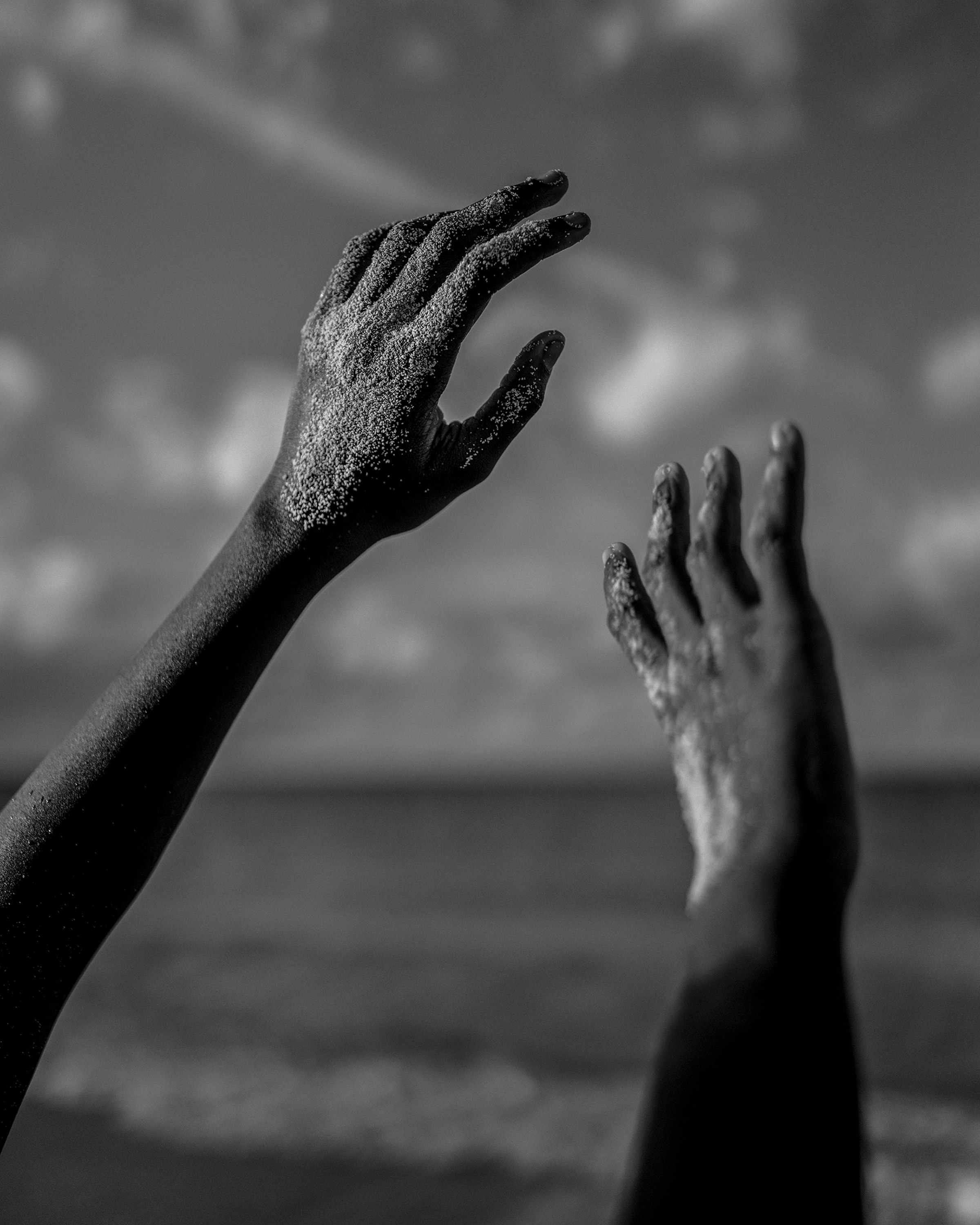 Two hands covered in sand