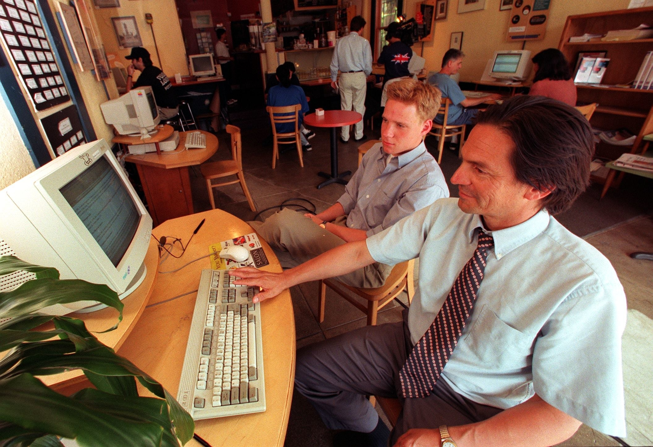 Two guys sitting in an internet cafe looking at a desktop PC