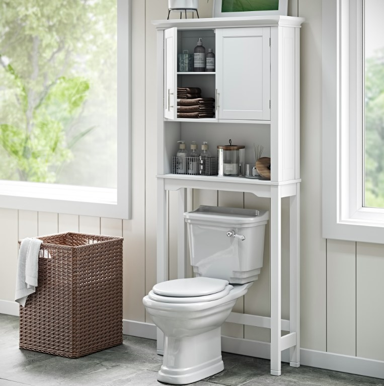The white space-saver installed over a white toilet and storing toiletries