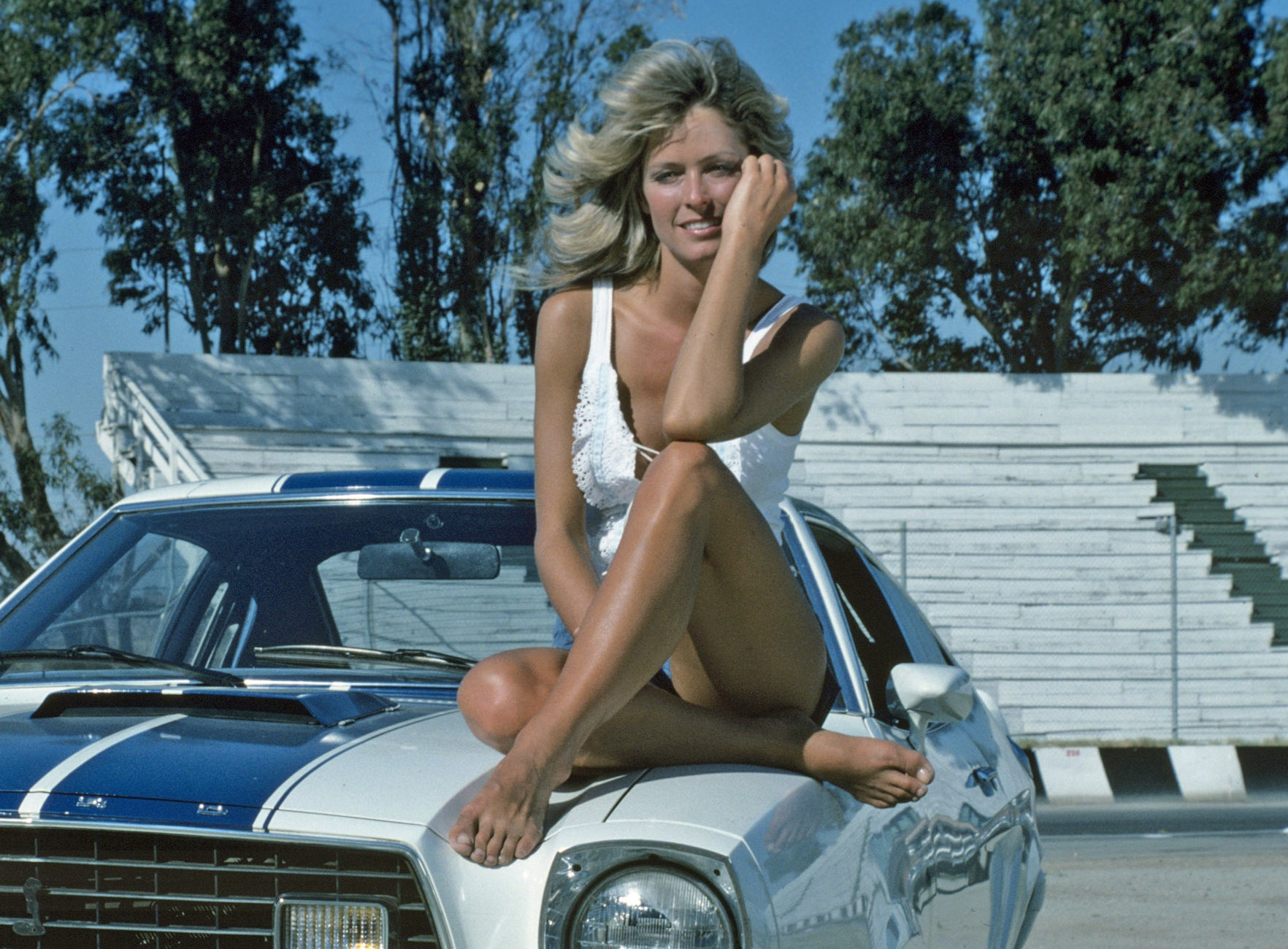 A young Farrah sits on top of a car in a white bathing suit