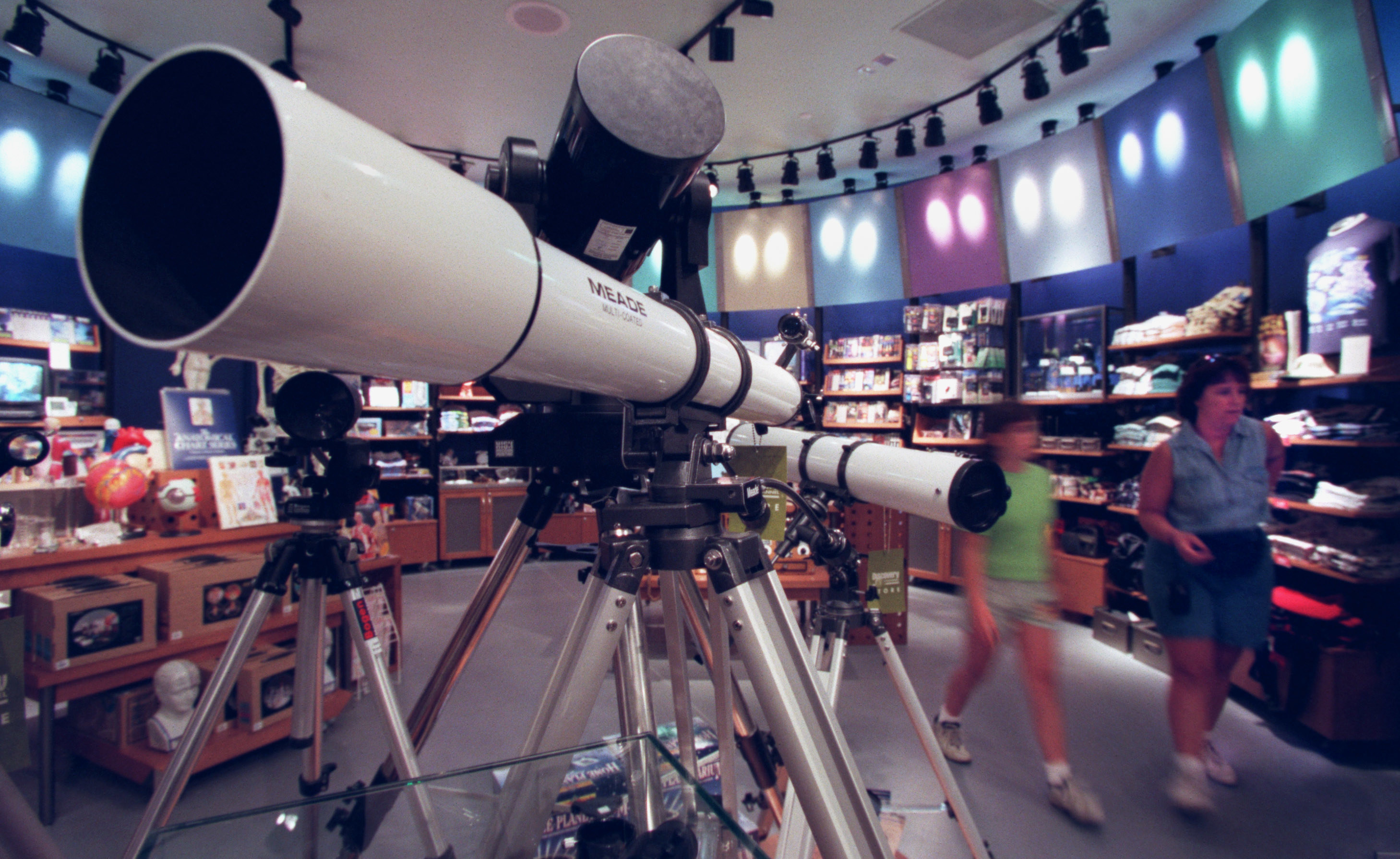 The back of Discovery Channel Store with shoppers, shirts stacked on the wall, and a collection of telescopes in the middle