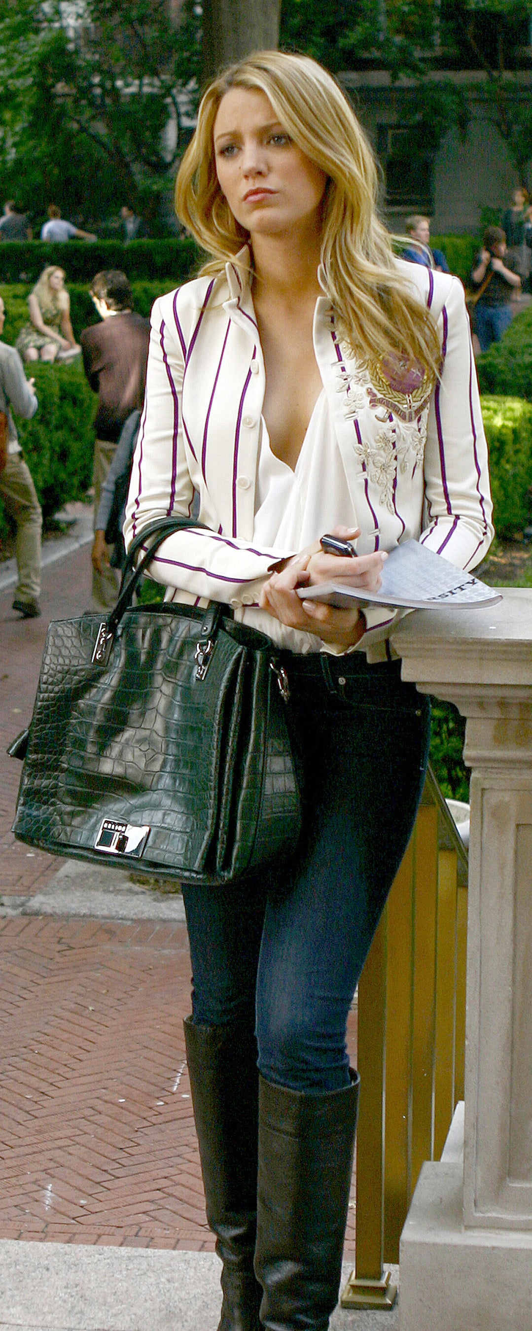 Serena in jeans, knee-high leather boots, a deep v neck blouse, and a pinstripe blazer