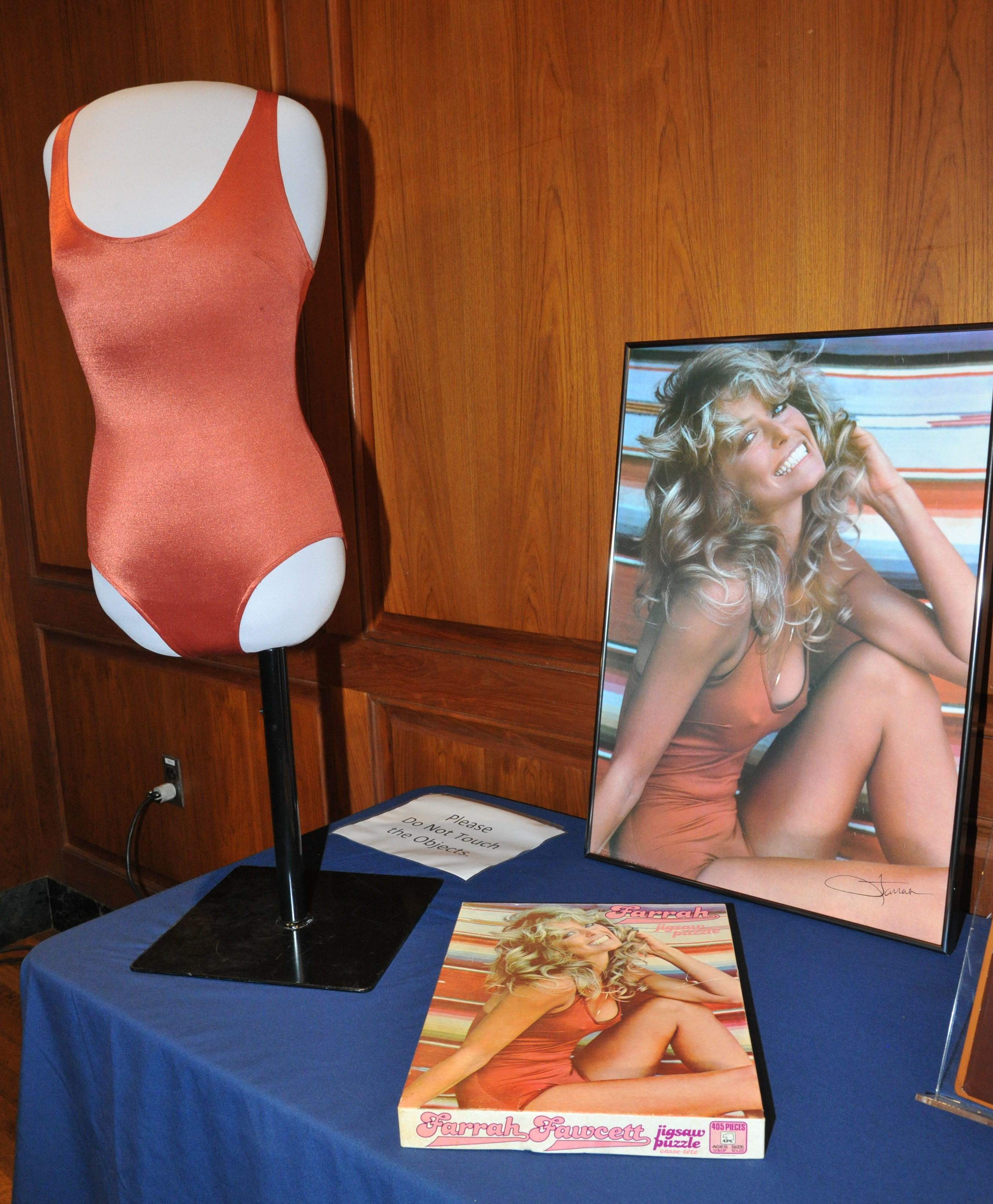 The bathing suit is seen on a mannequin in front of a copy of the poster at the museum