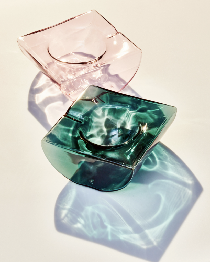 the glass ashtrays in teal and pink and we can see the dip in the glass made for resting the joint or incense