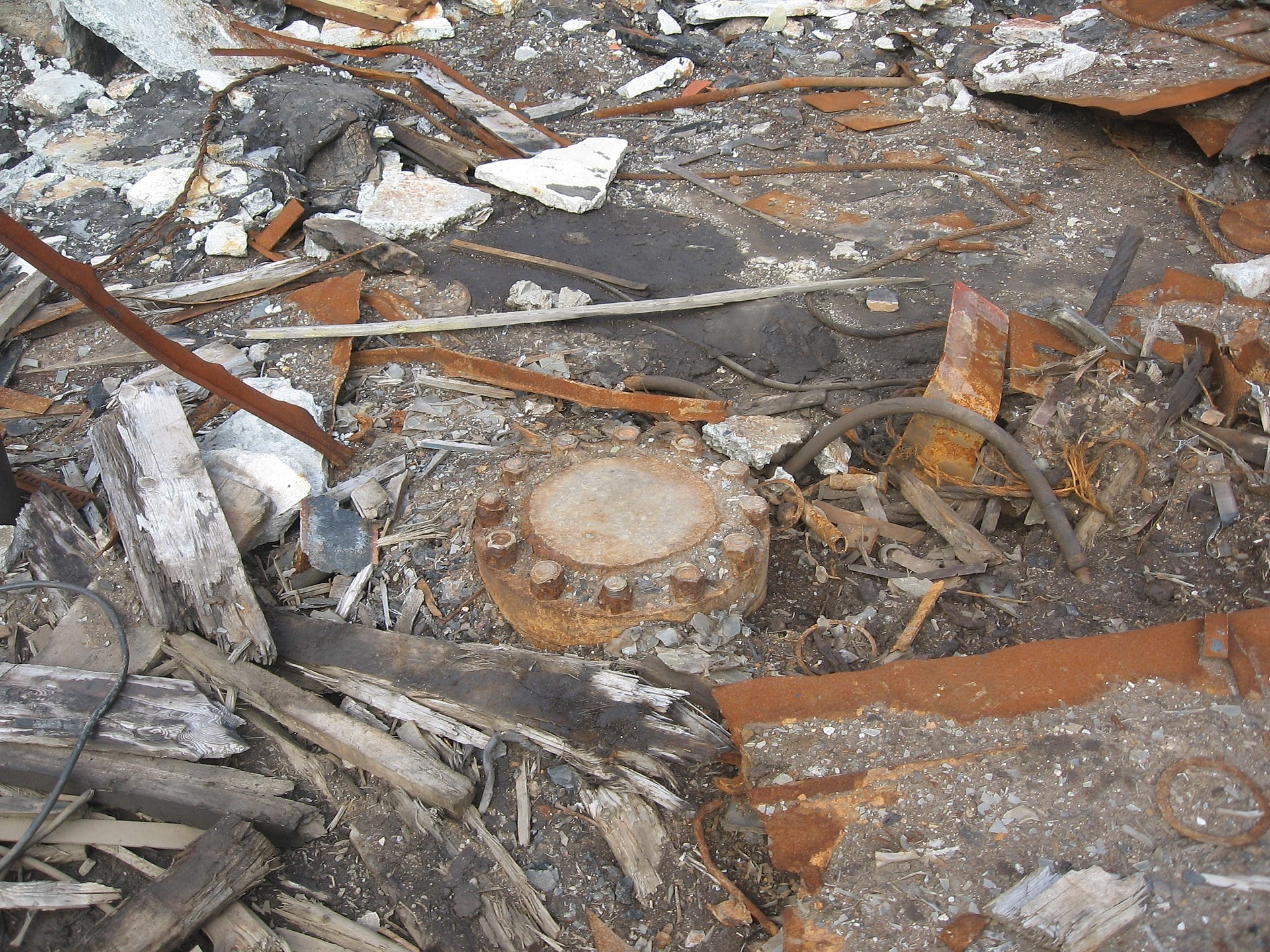 A round cap securely bolted over the hole, surrounded by rubble and debris