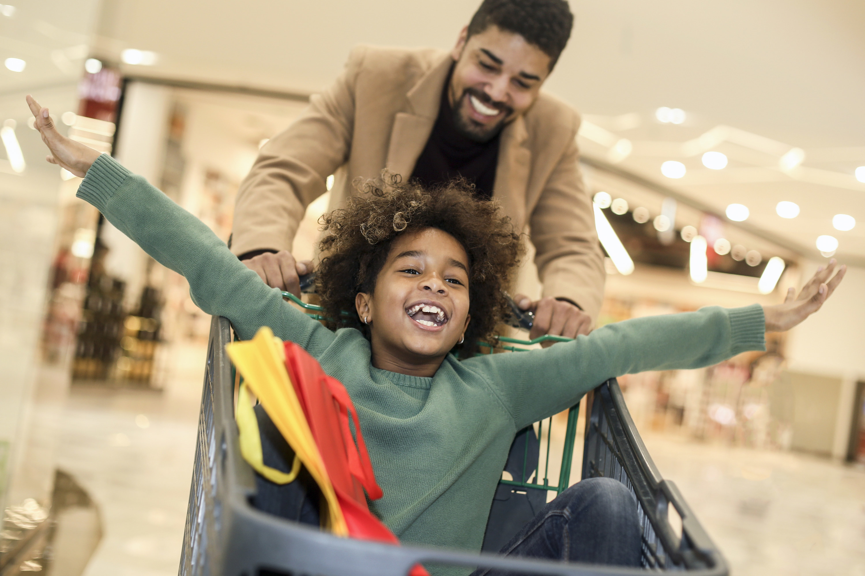 Young dad pushing a small child in a shopping cart