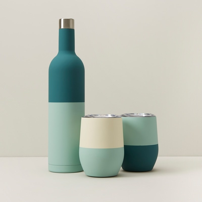 An insulated bottle next to two insulated wine tumblers