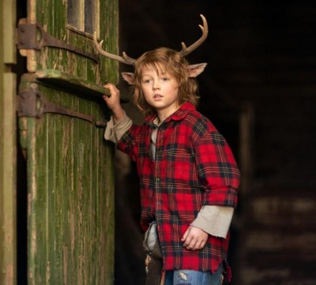 Gus wears a plaid shirt and stands near an open wooden door
