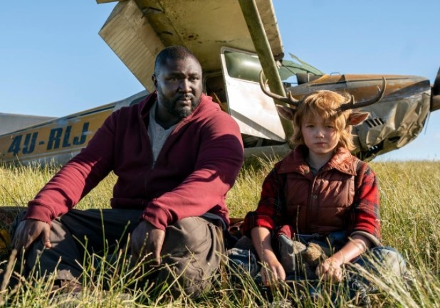 Jepperd sits next to Gus in a field with a broken-down plane behind them