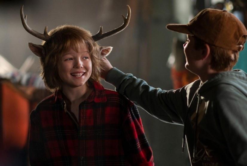 Gus smiles as a human boy touches his deer ears
