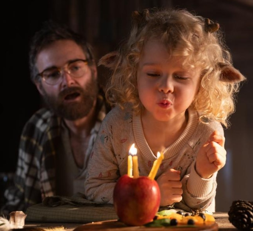 A young Gus blows out candles stuck in an apple while his father looks on