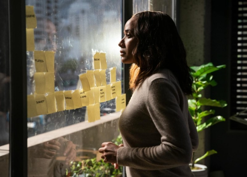 Aimee stands in her office and looks out a dirty window covered in Post-its
