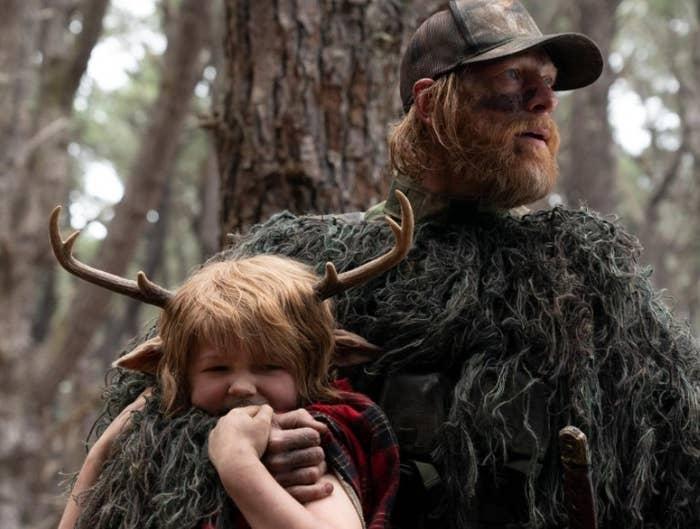 Gus is held in a headlock by a hunter