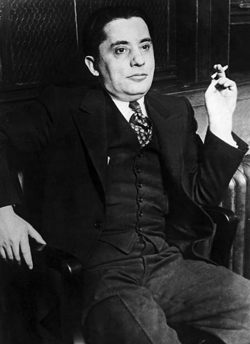 Jack Zuta wearing a three-piece suit, sitting in a chair, and holding a cigarette