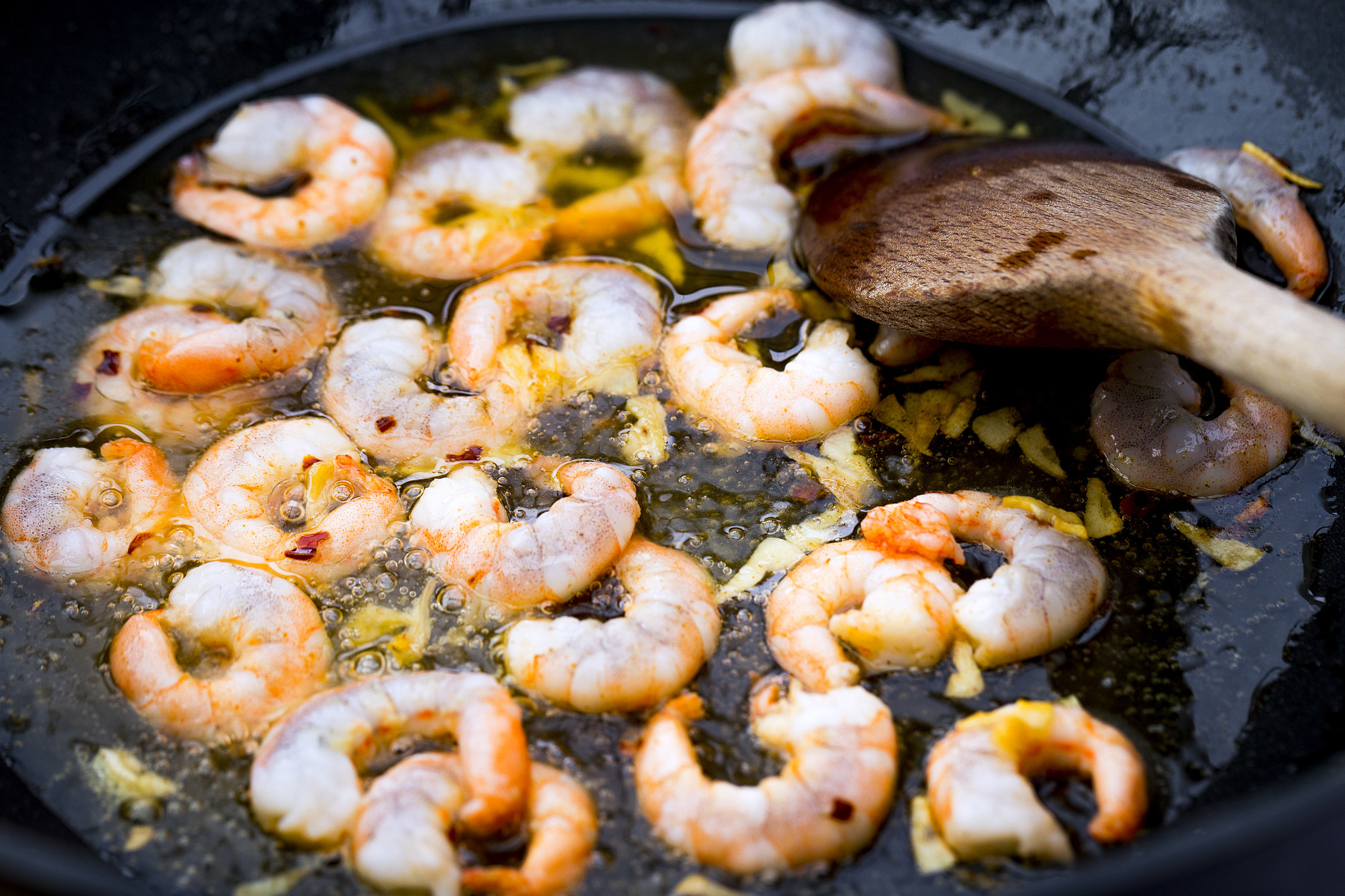 Garlic frying in oil with shrimp.