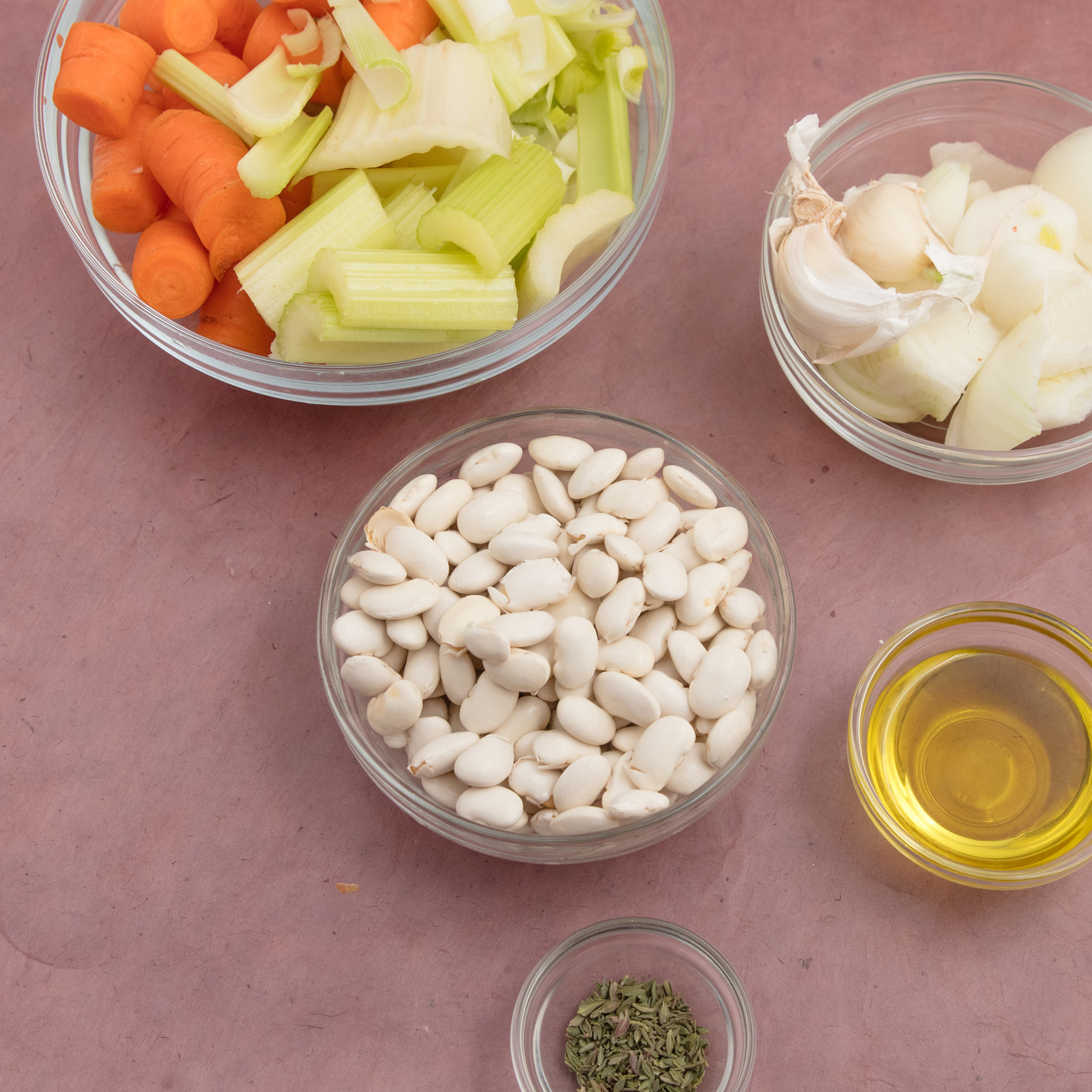Beans, veggies, stock, oil, and spices in small bowls to make soup.