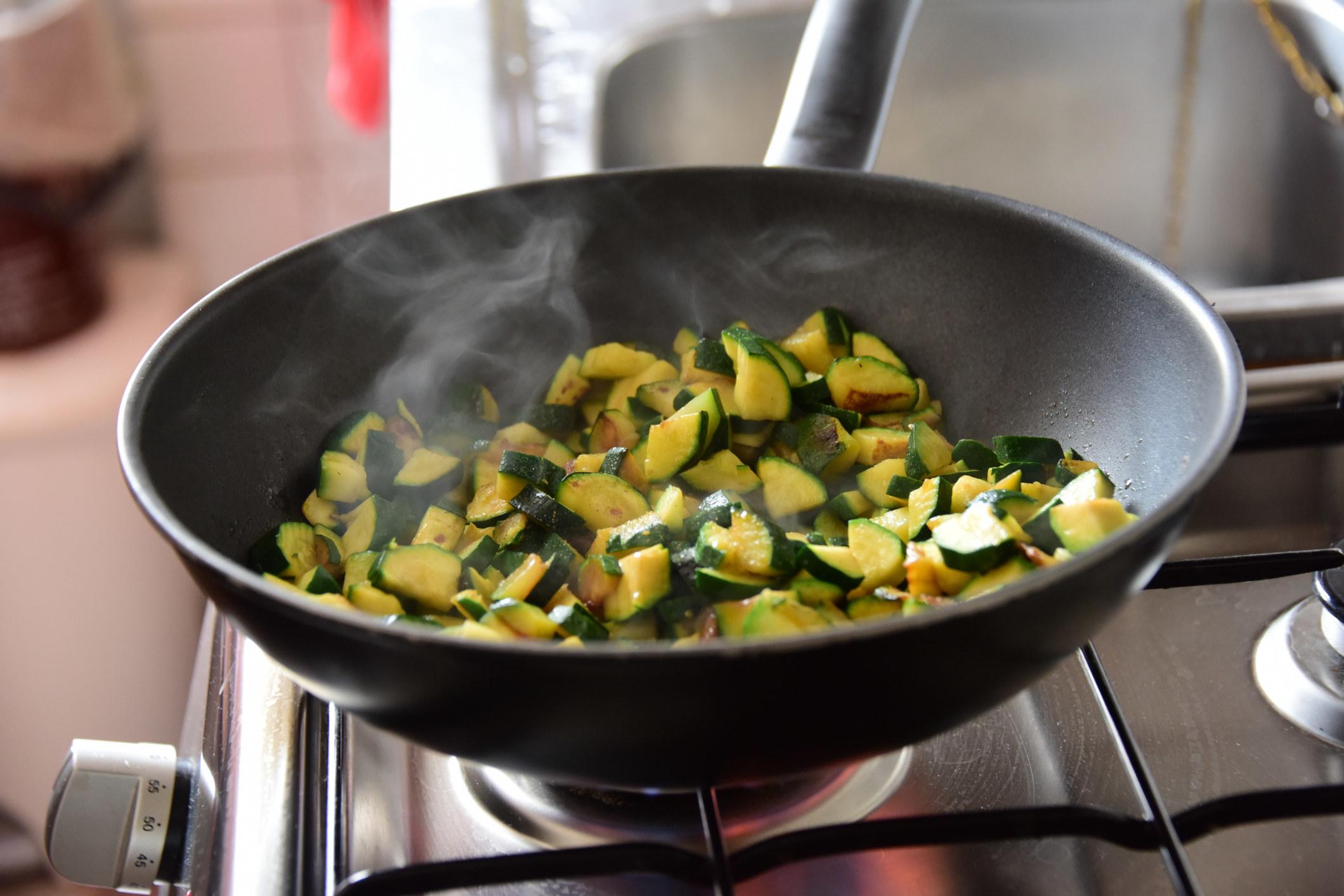 Sautéing zucchini in a skillet.