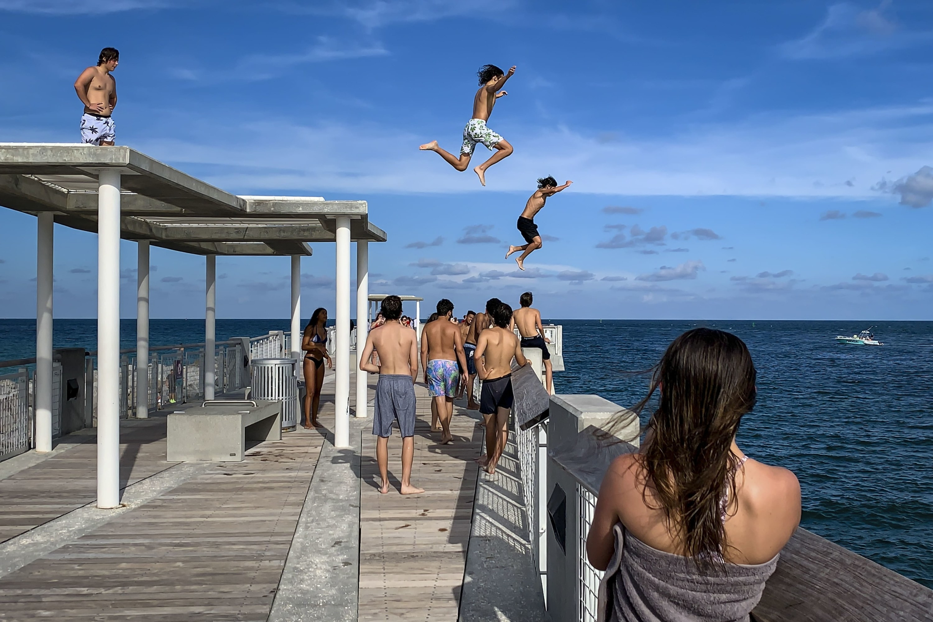 A group of kids jump off a dock while more kids watch