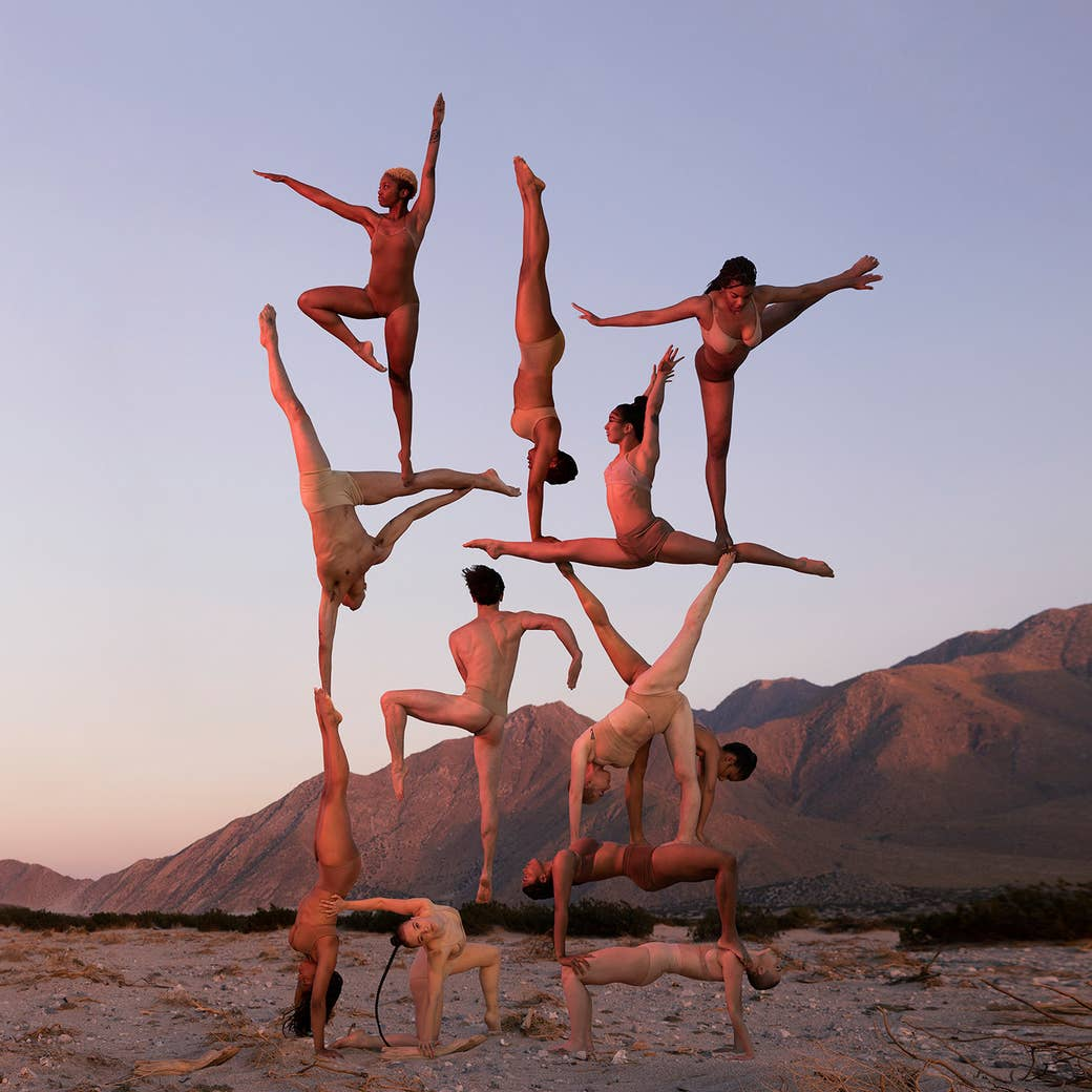 A group of acrobats stand on each other in the desert
