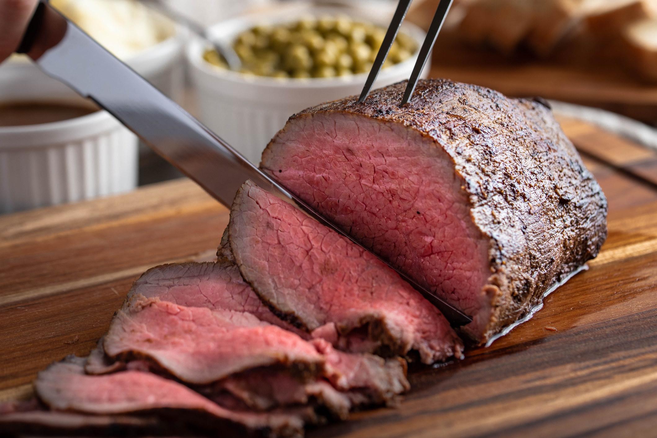 Slicing a medium-rare roast beef.