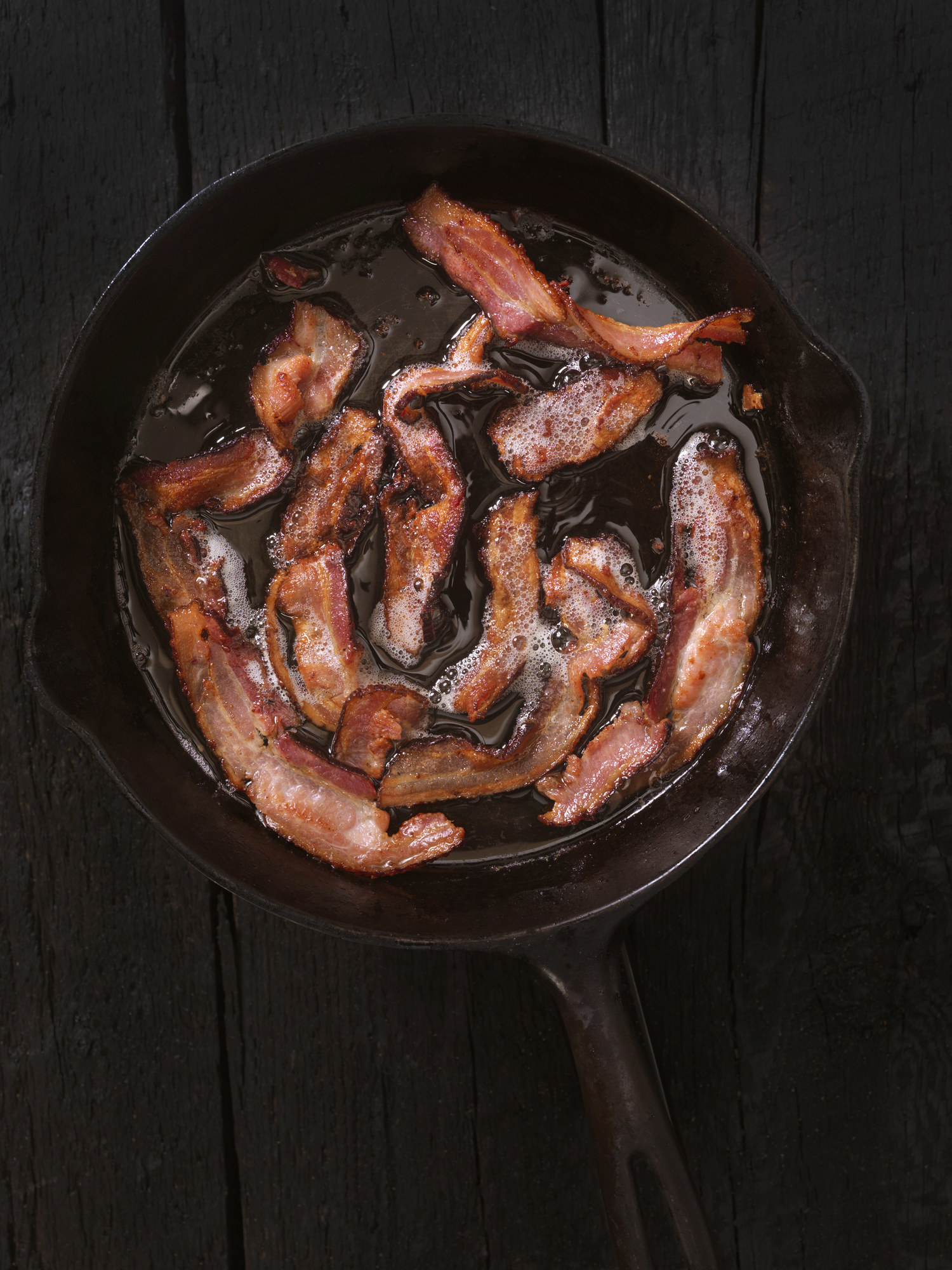 Bacon cooking in a sizzling cast iron skillet.