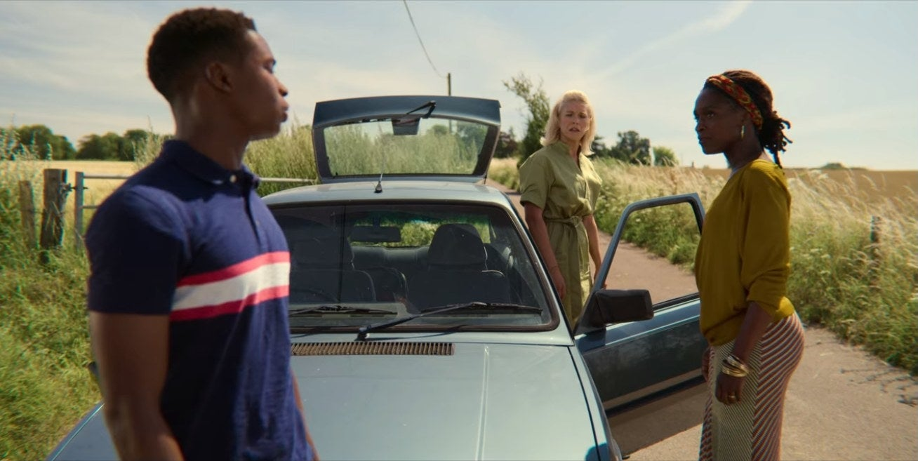Jackson stands near a car with his two moms.