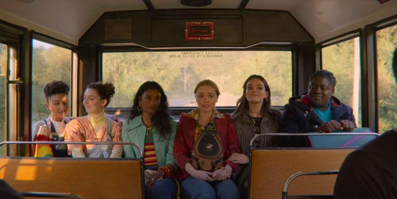 Ola, Lily, Olivia, Aimee, Maeve, and Viv ride in the back of a bus.