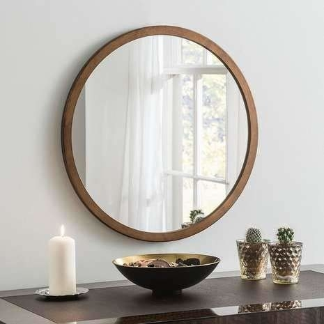 A circular mirror with a wooden border. It's placed on a wall above a table. Cacti, potpourri, and a white pillar candle are kept on the table.