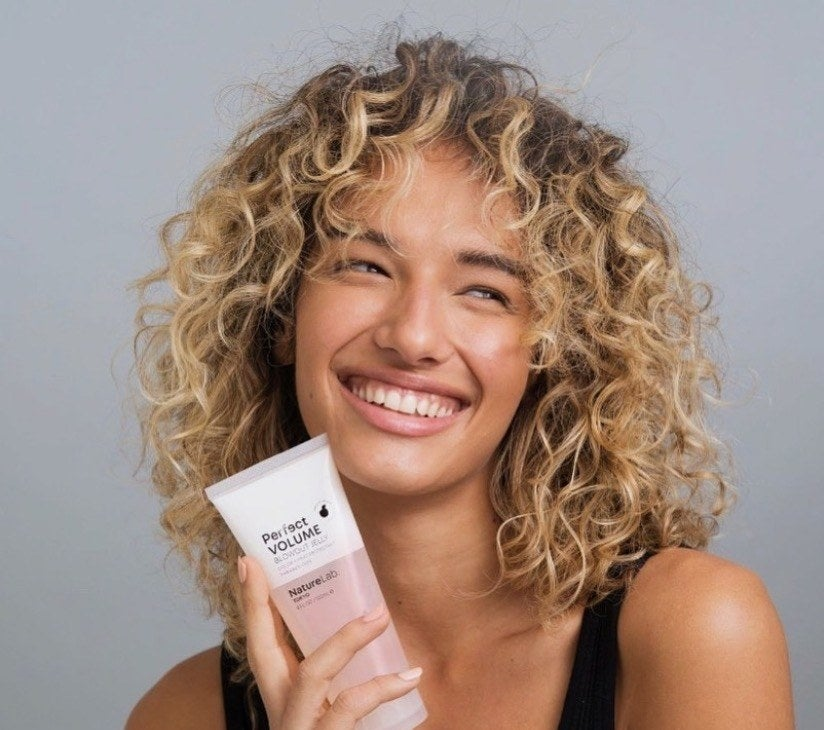 Reviewer with curly hair holding the volumizing jelly