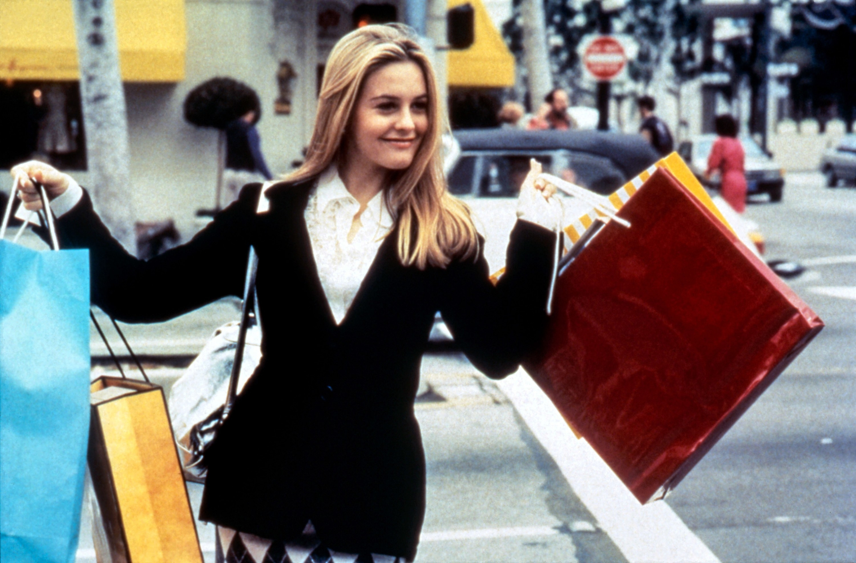 """Alicia Silverstone holds many shopping bags and smiles on set of """"Clueless"""""""