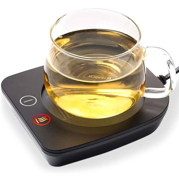 A desktop cup warmer in black with a cup of tea on it.